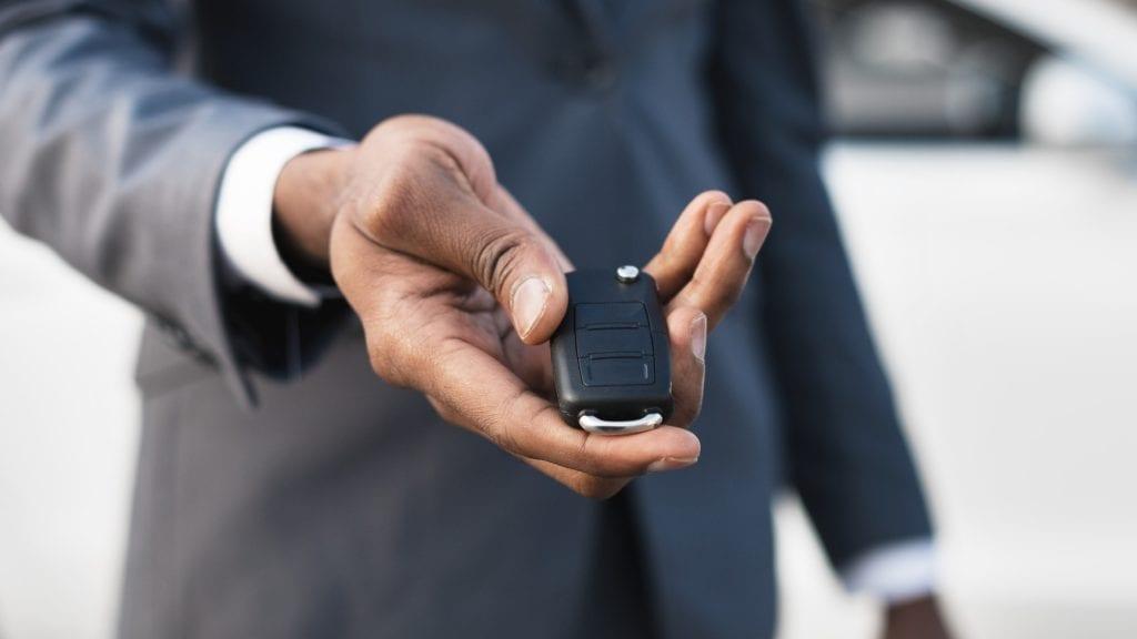 Car rental concept. Man holding car key in hand